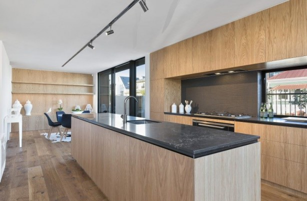 Wood themed kitchen with dark splashback tiles behind stove