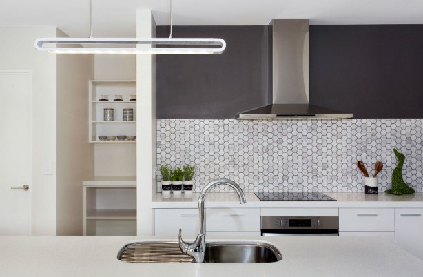 hex carrarra marble tiles behind stovetop